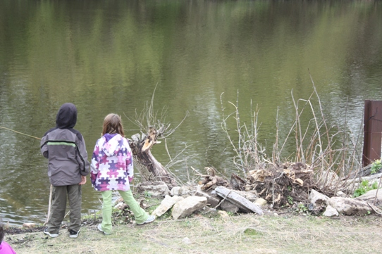 Two children standing beside a pond